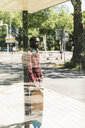 Cool young man with headphones, waiting at bus stop - UUF13851