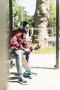 Cool young man with headphones, waiting at bus stop - UUF13854
