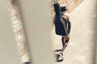 Young man walking in the city, carrying guitar case - UUF13857