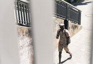 Young man walking in the city, carrying guitar case - UUF13866