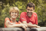 Mature couple leaning against log looking at camera smiling - CUF13207