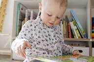 Female toddler reading book in playroom - CUF13286