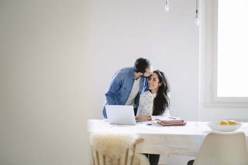 Young man kissing girlfriend working at home on laptop - CUF13304