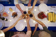 Group of people sitting at table, holding wine glasses, making a toast, overhead view - ISF06208