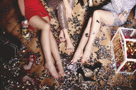 Three woman sitting on floor at party, shoes off, surrounded by glitter, low section - ISF06256