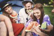 Young boho adult friends eating melon slices at festival - ISF06286