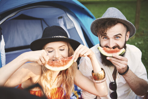 Young couple in trilbies making smiley face with melon slice at festival - ISF06289