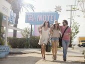 Friends walking past motel, Los Angeles, California, USA - CUF13378