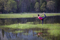 Woman practicing yoga tree pose by lake in Yosemite National Park, California, USA - ISF06384