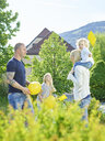 Austria, Wattens, happy family playing together in a park - CVF00622