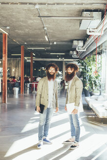 Portrait of male adult hipster twins holding digital tablet and laptop in office - CUF13573