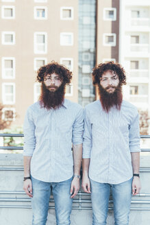 Portrait of identical male hipster twins standing on apartment roof terrace - CUF13582