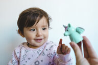 Portrait of smiling baby girl looking at  unicorn figure - GEMF02008