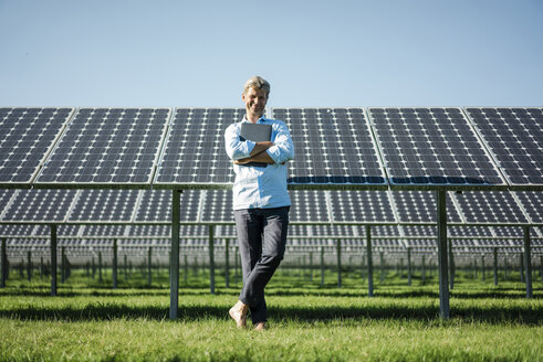 Mature man with laptop standing barefoot on meadow, solar plant - MOEF01118
