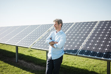 Smiling mature man leaning on solar panel - MOEF01121