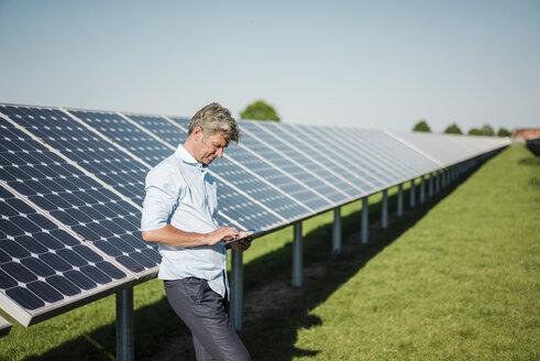 Businessman using tablet at solar park - MOEF01124