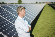 Smiling mature man standing in solar plant - MOEF01127