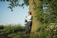 Businessman leaning on tree - MOEF01130