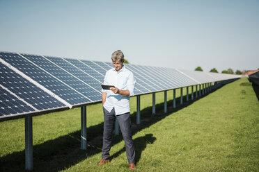 Businessman using tablet at solar park - MOEF01133