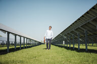 Mature man walking barefoot on meadow between solar panels - MOEF01136