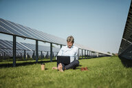 Mature man sitting barefoot on meadow, laptop and coffee to go cup, solar plant - MOEF01142