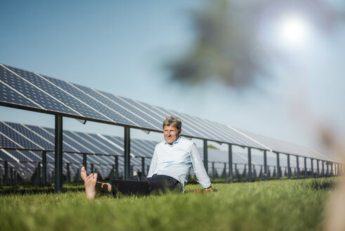 Mature man sitting barefoot on meadow, solar plant - MOEF01145