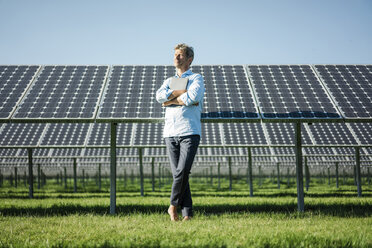 Mature man with laptop standing barefoot on meadow, solar plant - MOEF01148