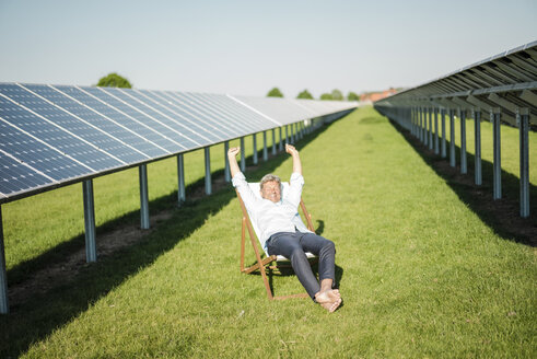 Mature man sitting in sun lounger, solar plant - MOEF01151