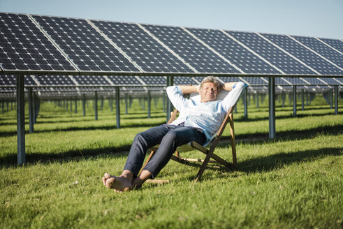 Mature man sitting in sun lounger, solar plant - MOEF01154