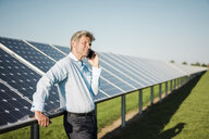 Businessman using smartphone at solar park - MOEF01172