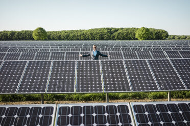 Mature man standing on panel in solar plant - MOEF01175