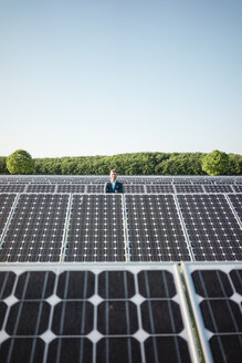 Mature man standing on panel in solar plant - MOEF01178