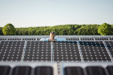 Mature man standing in solar plant - MOEF01181