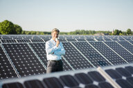 Mature man with smartphone standing in solar plant - MOEF01184