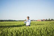 Businessman standing in grain field, holding miniature wind wheel - MOEF01193