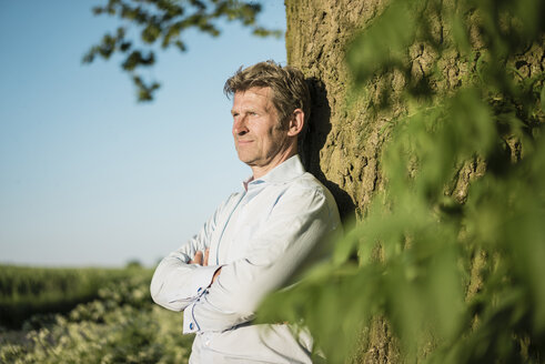 Businessman leaning on tree - MOEF01196