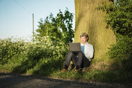 Businessman leaning against a tree using laptop - MOEF01202