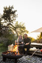 Couple sitting by fire pit in garden - CUF13722