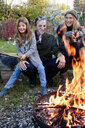Girl with mother and father sitting in garden with fire pit - CUF13725