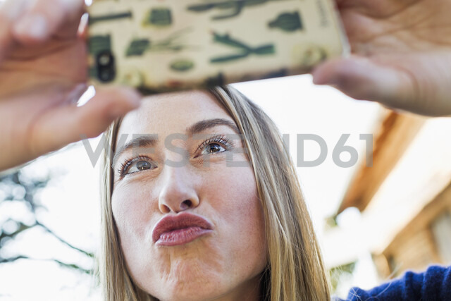 Mid adult woman posing for selfie with smartphone - CUF13734