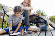 Girl drawing on decking with mother sitting close by, smiling - CUF13740