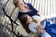 Mother and daughter relaxing on lounge chair, girl reading book - CUF13746