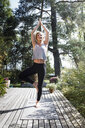 Young woman doing tree pose in garden - CUF13749