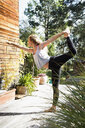 Young woman on one leg with arm out in yoga pose - CUF13770
