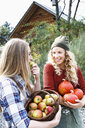 Two friends carrying homegrown produce, one woman eating apple - CUF13785