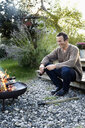 Mature man sitting by fire pit with beer, relaxing - CUF13803
