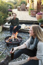 Man and woman sitting by fire pit with beer, relaxing - CUF13806