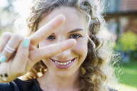 Young woman making peace sign with hand - CUF13812