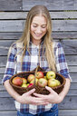 Mid adult woman holding basket of homegrown apples - CUF13821