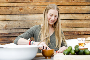 Mid adult woman preparing food at table outdoors - CUF13824